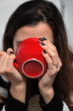 Het meisje drinkt thee van een rode grote kop Stock Foto's