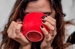 Het meisje drinkt thee van een rode kop Stock Foto's