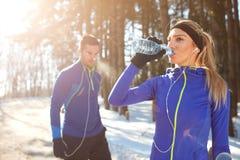 Het meisje drinkt water bij de opleiding in de winter in bos Royalty-vrije Stock Foto's