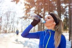 Het meisje drinkt water bij de opleiding openlucht Stock Foto's
