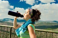 Het meisje drinkt water van een thermosfles stock fotografie