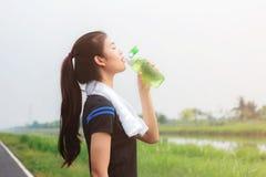 Het meisje is drinkwater in park royalty-vrije stock afbeelding