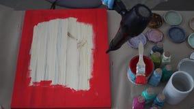 Het meisje droogt een beeld met de droogkap in een schort en in handschoenen De Blikken van de verf stock videobeelden