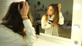 Het meisje droogt haar en kijkt in de spiegel stock footage