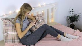 Het meisje drukt een bericht op de telefoon en droevig stock footage