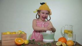 Het meisje drukt uit sap van een citroen stock videobeelden