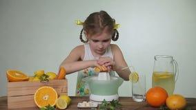 Het meisje drukt uit sap van een grapefruit stock videobeelden