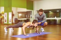 Het meisje drukte in gymnastiek met trainer Stock Fotografie