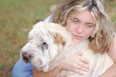 Het meisje drukte witte hond in Stock Foto's