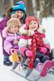 Het meisje duwt sleeën met twee jongere kinderen Stock Foto