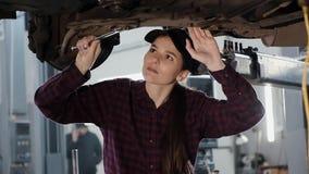Het meisje is een automobiele werktuigkundige, belast met het herstellen van de opschorting van de auto in het benzinestation stock videobeelden