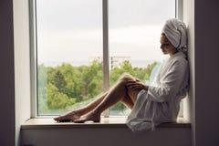 Het meisje in een badjas en een handdoek op hoofd zit op het venster royalty-vrije stock afbeelding
