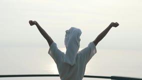 Het meisje in een badjas heft omhoog haar handen in de ochtend op stock videobeelden