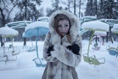 Het meisje in een beige bontjas en een kap bevindt zich op de achtergrond van de carrousel en koesterde zich stock foto's