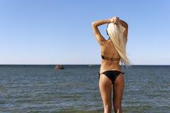 Het meisje in een bikini bekijkt het blauwe overzees Royalty-vrije Stock Afbeeldingen