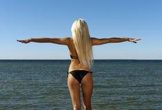 Het meisje in een bikini bekijkt het blauwe overzees Royalty-vrije Stock Foto