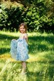 Het meisje in een blauwe kleding dient binnen de zomertuin in Stock Foto's