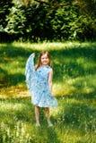 Het meisje in een blauwe kleding dient binnen de zomertuin in Stock Afbeelding