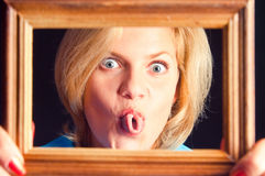 Het meisje in een blauwe kleding zet uit de tong Royalty-vrije Stock Foto