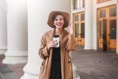 Het meisje in een bruine laag een bruine hoed loopt en stelt in het stadsbinnenland Het meisje glimlacht, controlerend haar smart Stock Foto's