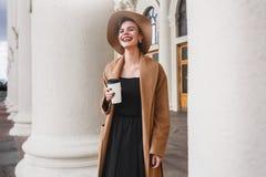 Het meisje in een bruine laag een bruine hoed loopt en stelt in het stadsbinnenland Het meisje glimlacht, controlerend haar smart Royalty-vrije Stock Foto's