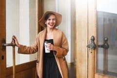 Het meisje in een bruine laag een bruine hoed loopt en stelt in het stadsbinnenland Het meisje glimlacht, controlerend haar smart Royalty-vrije Stock Fotografie