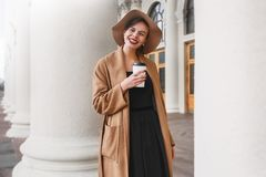 Het meisje in een bruine laag een bruine hoed loopt en stelt in het stadsbinnenland Het meisje glimlacht, controlerend haar smart Royalty-vrije Stock Afbeeldingen
