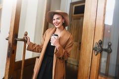 Het meisje in een bruine laag een bruine hoed loopt en stelt in het stadsbinnenland Het meisje glimlacht, controlerend haar smart Royalty-vrije Stock Foto