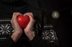 Het meisje in een donkere de wintersweater houdt groot rood hart in hand royalty-vrije stock foto's