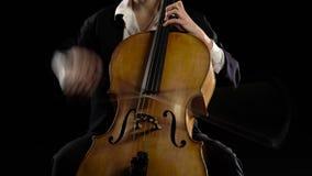 Het meisje in een donkere ruimte speelt een cello repeterend een samenstelling Zwarte achtergrond stock footage