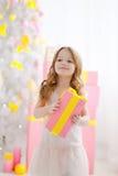 Het meisje in een elegante kleding stelt een gift voor Stock Afbeelding