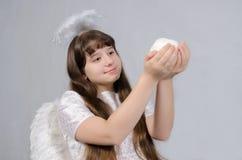 Het meisje in een engelenkostuum houdt een sneeuwbal stock foto