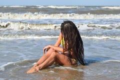 Het meisje in een geel badpak op het strand Meisje met zwarte haarzitting in gebogen zeewaterhoofd royalty-vrije stock fotografie
