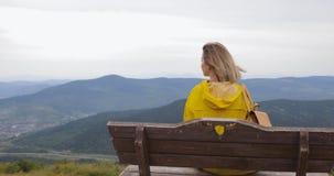 Het meisje in een gele regenjas zit bovenop een berg, genietend van een mooie mening stock videobeelden