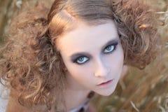 Het meisje in een gras Stock Afbeeldingen