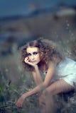 Het meisje in een gras Stock Foto