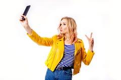 Het meisje in een helder geel jasje maakt een selfie voor sociale netwerken op smartphone stock foto's