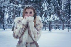 Het meisje in een heldere bontjas met stromend haar en de sneeuw op haar haar zetten haar handen aan haar gezicht tegen de achter stock afbeelding
