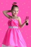 Het meisje in een heldere kleding kijkt in de spiegel en doend maak Royalty-vrije Stock Fotografie