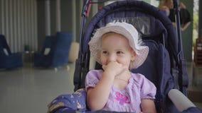 Het meisje in een hoed zit in een blauwe wandelwagen en likt haar mond met haar hand, langzame motie stock videobeelden