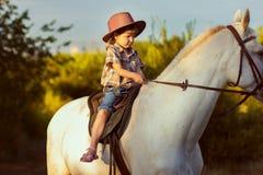 Het meisje in een hoed zit op een paard Stock Afbeelding