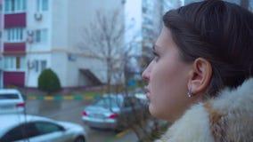 Het meisje in een jasje met een kap met een kapsel kijkt aan de kant stock footage
