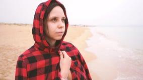 Het meisje in een kap op het strand kijkt zorgvuldig in de afstand stock video
