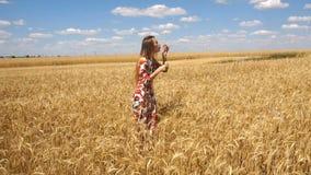 Het meisje in een kleding die zich op een gebied bevinden en zet bellen in langzame motie stock videobeelden