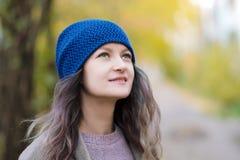 Het meisje in een laag en een blauwe hoed op een achtergrond van de herfstbomen en esdoorn gaat weg royalty-vrije stock foto
