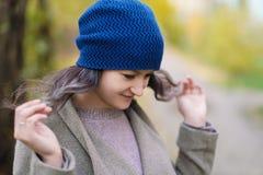 Het meisje in een laag en een blauwe hoed op een achtergrond van de herfstbomen en esdoorn gaat weg royalty-vrije stock afbeeldingen