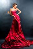 Het meisje in een lange rode kleding houdt Royalty-vrije Stock Afbeeldingen