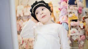 Het meisje in een leuke zwarte hoed bekijkt zich in de spiegel Stock Afbeeldingen
