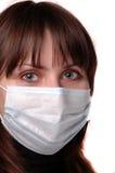 Het meisje in een medisch masker stock foto's