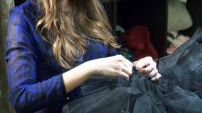 Het meisje is een naaister die in een naaiende workshop werken stock videobeelden